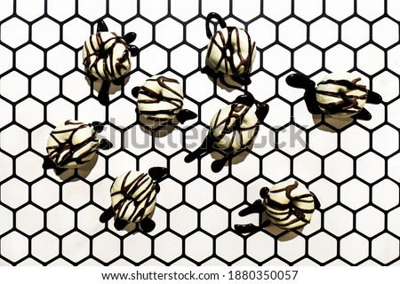 Small white donuts with dark chocolate glazing on geometric hexagonal background. Minimalistic chromatic white and black picture of delicious doughnuts.