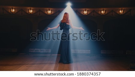 Young woman in elegant dress gesticulating and talking passionately with audience then walking away in end of performance in theater Royalty-Free Stock Photo #1880374357