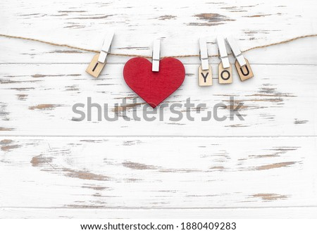 "The word ""I love you"" with wooden letters and heart shape. Love theme. Wooden cubes with the word on pegs. Valentines day"