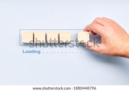 Loading, hand putting wood cube in progress bar. Download progress