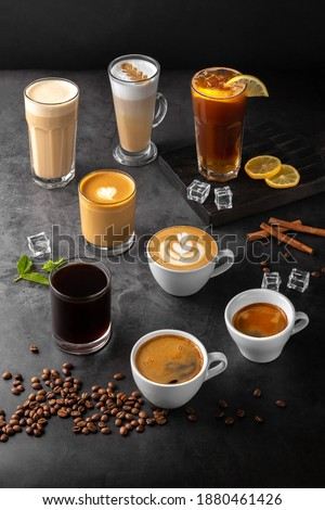still life composition with glasses and cups of espresso, latte americano, brewed, raf coffee, cappuccino with rosetta latte and green matcha art and roasted coffee beans on a black marble background Royalty-Free Stock Photo #1880461426