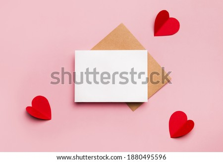 Mockup blank greeting card for valentines day. Composition with red hearts for Valentine's Day on a pale pink background. Flat lay. Love and relationships concept. Royalty-Free Stock Photo #1880495596