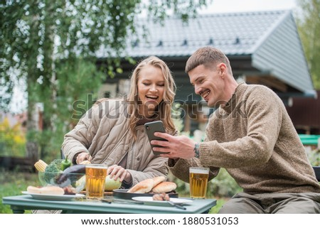 The husband shows his wife the phone screen with something funny. They smile and have a good mood, spending time together on a picnic with barbecue and beer