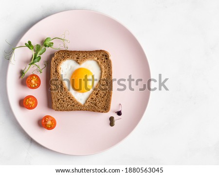 Heart shaped egg in tosted slice of rye bread on pink ceramic plate. St Valentine's day concept. Love breakfast design. Homemade creative food. Healthy sandwich. Festive lunch or breakfast. Copy space