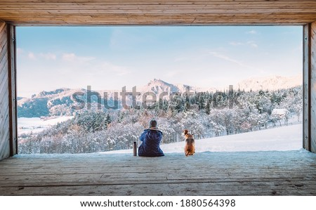 Woman with thermos flask sitting with her beagle dog in the big wooden hangar with a huge panoramic window and looking on the snowy mountain landscape. Human and pets relatives concept image.  Royalty-Free Stock Photo #1880564398