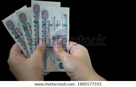 A female hand holding a hundred pounds paper on black background Egyptian currency  Royalty-Free Stock Photo #1880577592