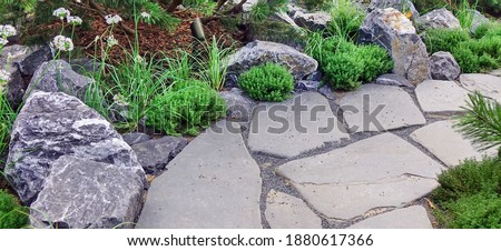 Backyard Garden Modern Design Landscaping. Landscaped Back Yard. Decorative Garden With Pathway Or Walkway From Stone And Rocks Or Gravel. Back Yard Or Park Lawn With Stony Natural landscaping. Royalty-Free Stock Photo #1880617366
