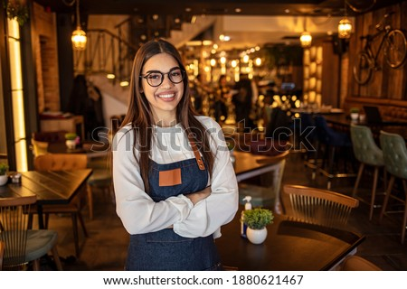 Portrait of a beautiful waitress wearing an apron, smiling at camera. Portrait of positive young woman working professional confectioner in own coffee shop, looking at camera with toothy smile.