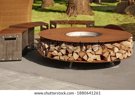Round Patio Iron Fire Pit Table For Outdoor Leisure Party. Steel Rounded Fire Pit With Grill Top On Backyard Party Place. Grill Appliance And Fireplace On The Back Yard Lawn. Royalty-Free Stock Photo #1880641261