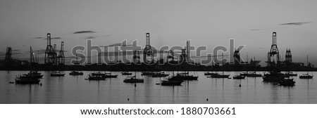 Panoramic image at dawn with anchored sailboats and port in the background