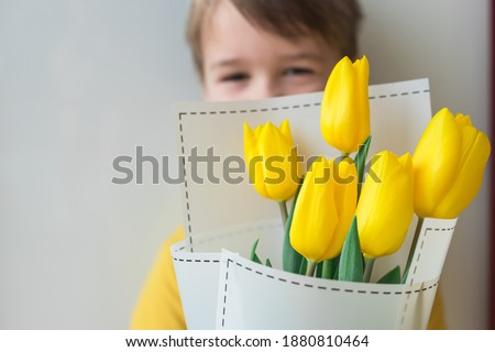 Toddler happy and smiling boy with a large bouquet of yellow tulips in Mothers Day. Portrait of a beautiful little kid on a gray background. Spring background Royalty-Free Stock Photo #1880810464
