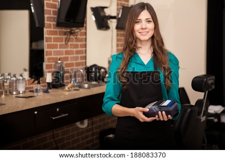 Beautiful brunette holding a credit card terminal in front of a barber shop and smiling