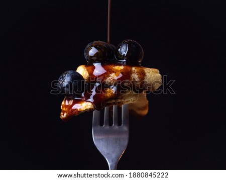 Maple syrup drip on blueberry pancakes in a vertical fork black background. Traditional food for breakfast or brunch. Tasty pancakes with fruit and maple syrup. Food photography