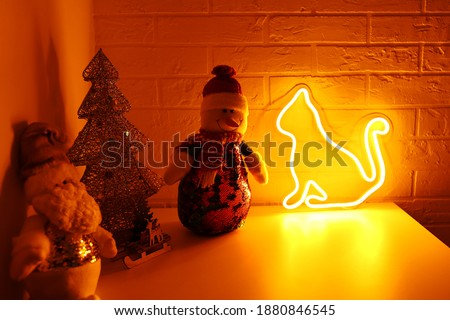 Neon sign yellow cat in the decor. Merry Christmas background. New Year. Trendy style. Neon sign. Custom neon. Home decor.