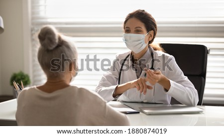 Female doctor in medical facial mask have consultation with elderly patient during covid-19 pandemics. Woman GP in facemask talk consult mature client in clinic or hospital. Coronavirus concept. Royalty-Free Stock Photo #1880874019