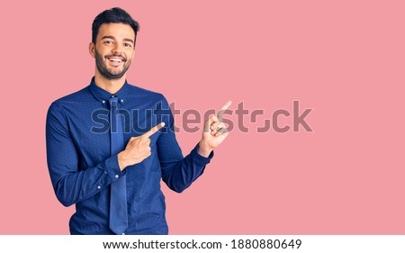 Young handsome hispanic man wearing business clothes smiling and looking at the camera pointing with two hands and fingers to the side.  Royalty-Free Stock Photo #1880880649