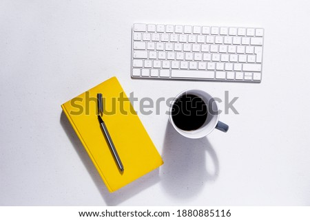 White table with white keyboard next to ultimate gray coffee mug and illuminating yellow notebooks with color of the year pencils