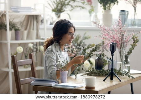 Do it yourself. Enthusiastic young woman giving professional course webinar by flower arranging. Florist recording video lesson on smartphone webcam at creative studio. Promoting hobby business online Royalty-Free Stock Photo #1880978272