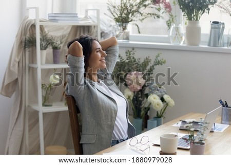Moment of relax. Serene businesswoman florist owner of flower delivery service rest of computer work. Smiling calm lady floral decor specialist hold hands behind head enjoy quietness breath fresh air Royalty-Free Stock Photo #1880979028