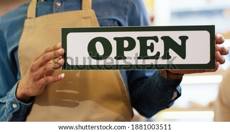 Close up shot of African American male hands holding Open sign indoors in bakery shop. Reopening business. Small business. Man worker entrepreneur holds Open card indoor.