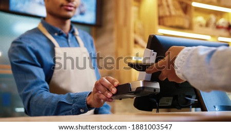 Close up of African American male seller in face mask and protective black gloves selling baked fresh bread in bakery shop. Client paying with credit card on device buying baking. Business concept