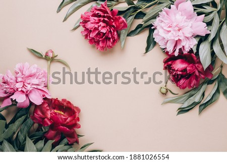 Frame of beautiful peonies on beige background. Mother's day or other holiday background.