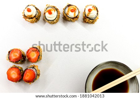 set of sushi rolls with salmon avocado and strawberry on the white surface and also soya sauce. copy space sushi rolls uramaki.
