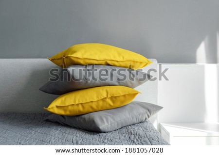 Color pillows illuminating ultimate gray pile on bed Two trendy 2021 colors of years Modern interior design Cozy textile Sweet home Royalty-Free Stock Photo #1881057028