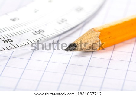 A small pencil with a protractor laying on graph paper.
