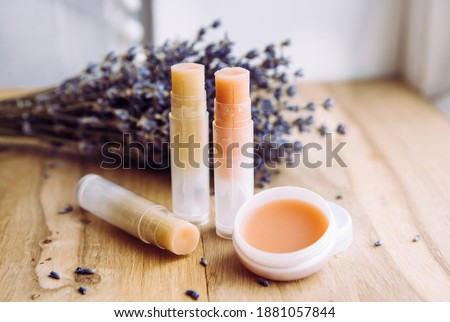 Make homemade natural organic ingredients lip balm. Handmade lip balm and lipstick inside container on natural wooden background and lavender for decoration. Royalty-Free Stock Photo #1881057844