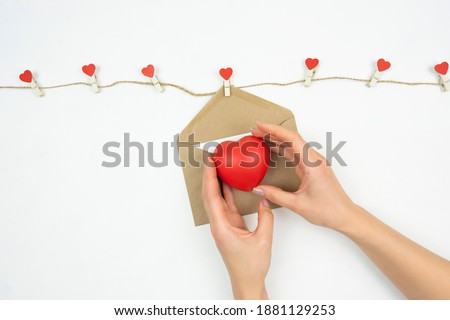 A woman holds a red heart as a symbol of Valentine's Day
