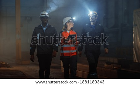 Three Diverse Multicultural Heavy Industry Engineers and Workers in Uniform Walk in Dark Steel Factory Using Flashlights on Their Hard Hats. Female Industrial Contractor is Using a Tablet Computer. Royalty-Free Stock Photo #1881180343