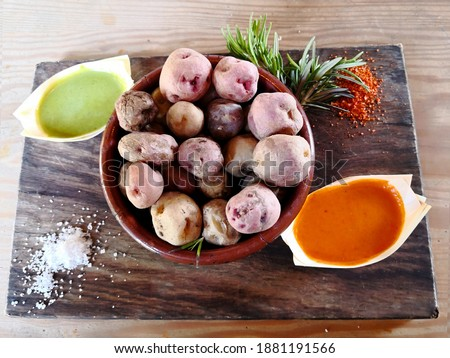 """Boiled """"wrinkled"""" potatoes prepared following canarian recipe on wooden plate and two red and green local dressings """"mojo"""" in a restaurant in Teguise city in Lanzarote, Canary islands. Selective focus Royalty-Free Stock Photo #1881191566"""
