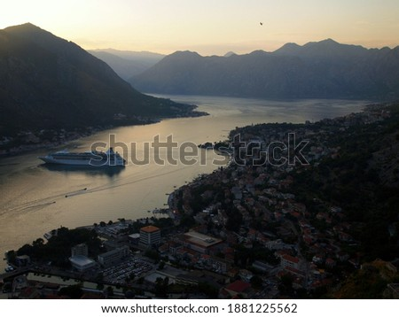 Bay of Kotor in twilight right after sunset. Bird's eye view of the bay. Pictured are a cruise ship, city of Kotor, the bay, surrounding landscape with mountains and a bird in flight. Warm tones.