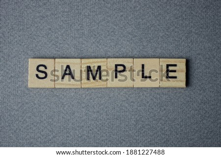 text the word sample from brown wooden small letters with black font on an gray table Royalty-Free Stock Photo #1881227488