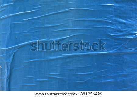 Beautiful waved creased blue street poster paper texture, creative abstract street appeal flyer background texture Royalty-Free Stock Photo #1881256426
