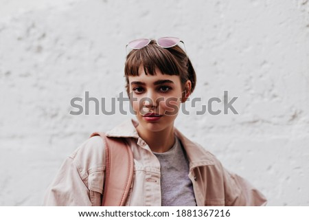 Cool girl with short hair looking into camera on background on white backdrop. Brunette lady with glass in beige outside posing on backdrop of wall.. Royalty-Free Stock Photo #1881367216