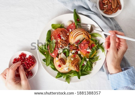 Eating fruits citrus salad with nuts, green lettuce. Balanced food. Top view of woman hands with plate of meal of Spinach with orange, grapefruit, apples, pecans Royalty-Free Stock Photo #1881388357