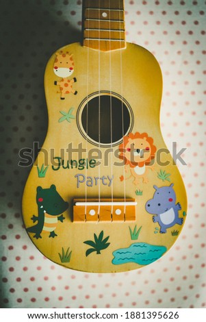 A top view of a ukulele decorated with cartoon characters on the table under the lights