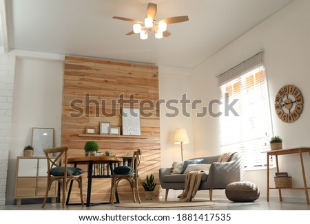 Stylish living room interior with modern ceiling fan, low angle view Royalty-Free Stock Photo #1881417535