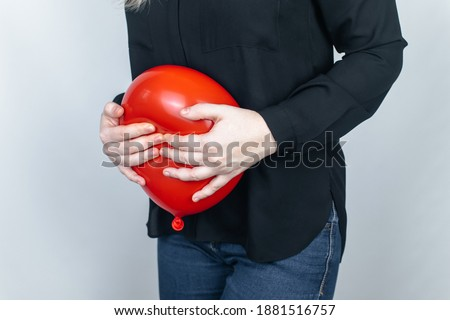 Bloating and flatulence concept. The woman holds a red balloon near the abdomen, which symbolizes bloating. Intestinal tract and digestive system. Problems with flatulence adn gastrointestinal tract Royalty-Free Stock Photo #1881516757
