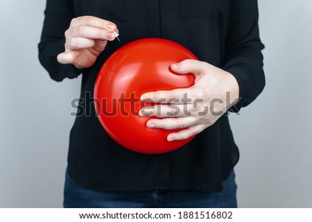 Conceptual photography. The woman holds a red ball near his belly, which symbolizes bloating and flatulence. Then she brings a needle to it to burst the balloon and thus get rid of the problem. Royalty-Free Stock Photo #1881516802