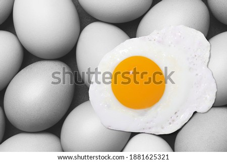 Fried eggs are pictured on a black and white image of multiple eggs, suitable for use in food media
