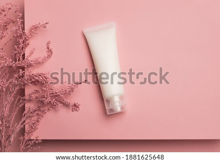 Cosmetic cream tube packaging on platform and flower branch on pastel pink background. Beauty and skincare concept, mockup for design. Minimal trendy composition. Top view, flat lay, copy space
