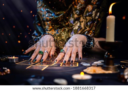 Cartomancy. A fortune teller reads Tarot cards. On the table are candles and fortune-telling objects and sparks. Hands close up. The concept of divination, astrology and esotericism Royalty-Free Stock Photo #1881668317