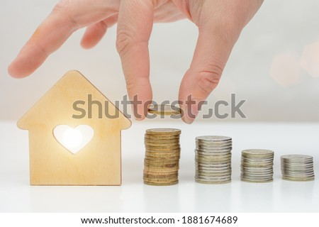 on a light background stacks of coins and a house. Hand adding a coin. The concept is the accumulation of money, the pursuit of your goal, the dream of your own real estate. Horizontal photo.