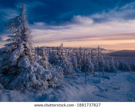 Scenic snowy landscape with a view from a mounatin range to the valley, snow, sky,clouds,sky,sunlight.Spruce trees with rime, scenic landscape. Jeseniky.Czech republic. Royalty-Free Stock Photo #1881737827