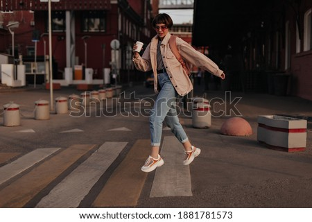 Cool woman in beige jacket jumping at street. Girl with short hair in jeans, glasses and light sneakers with backpack and cup of tea posing outside.. Royalty-Free Stock Photo #1881781573