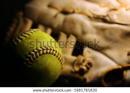 A yellow softball in front of a brown glove.