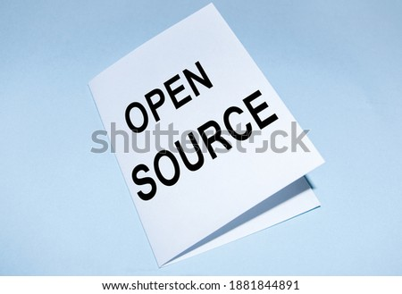 Open source text on a white sheet, on a blue background. A concept photo showing the software whose source code is freely available.